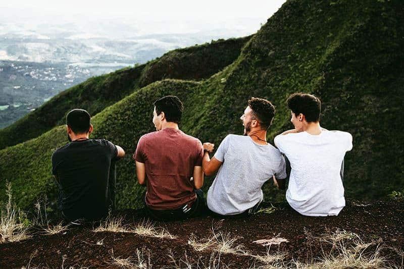 vänner som sitter framför kullarna