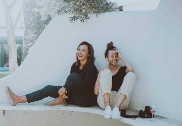 två vänner sitter på golvet och skrattar