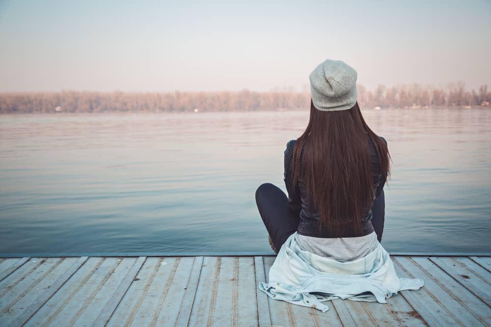 Flickasammanträde på pir och titta på floden