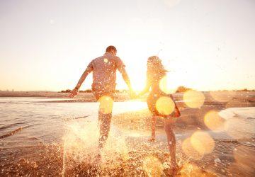lyckliga par springer på stranden
