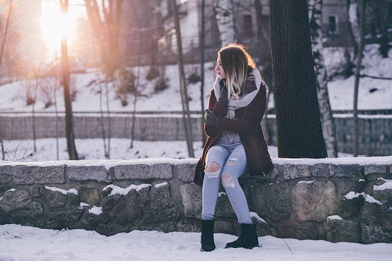 kvinna sitter på stenmur i snö