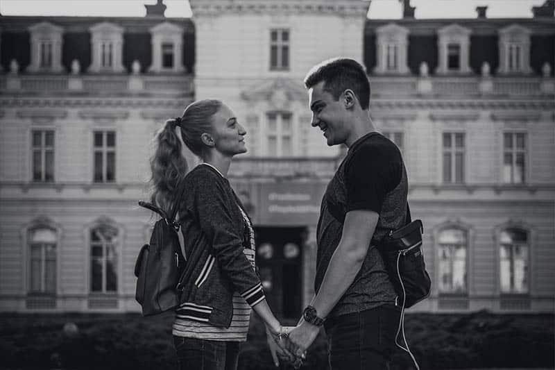 svartvitt foto av man och kvinna som håller händer