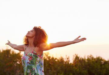 kvinna med händer spridda njuta av naturen
