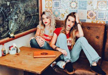 två fashionabla kvinnor poserar i restaurangen