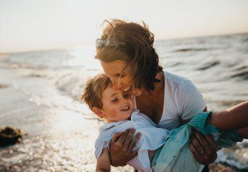 kvinnor med barn leende på stranden