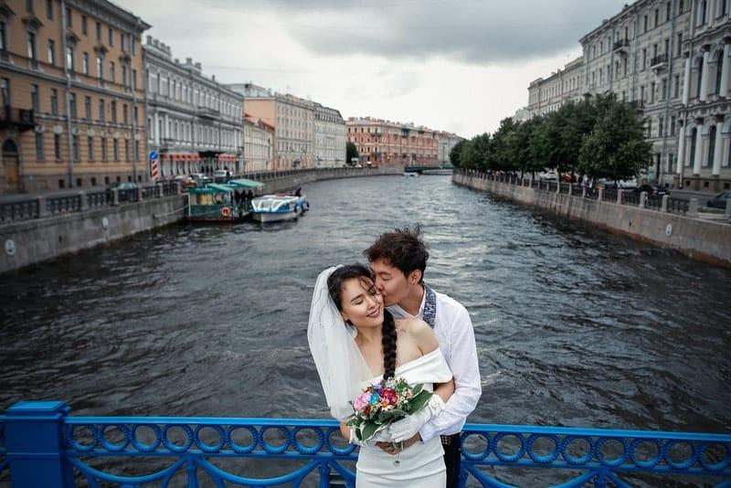 brudgummen och bruden i ett omfamning på bron med det blå staketet