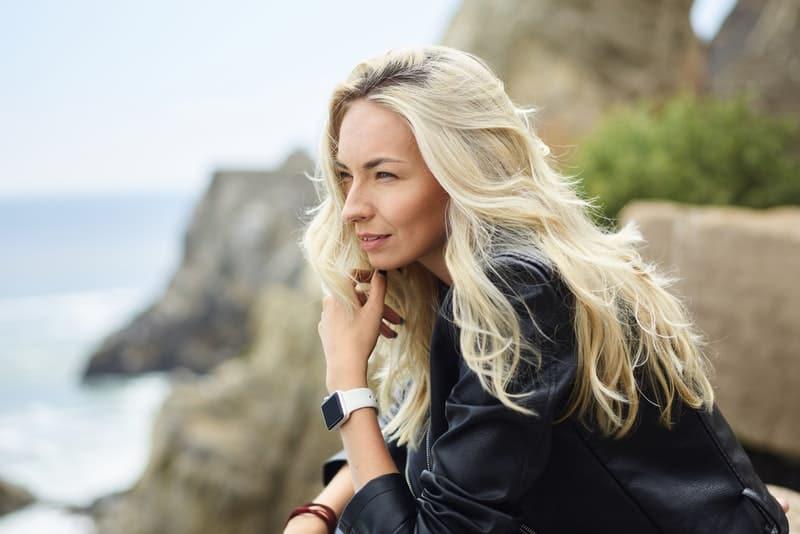 en blondin i en svart jacka står på en klippa ovanför havet och tänker