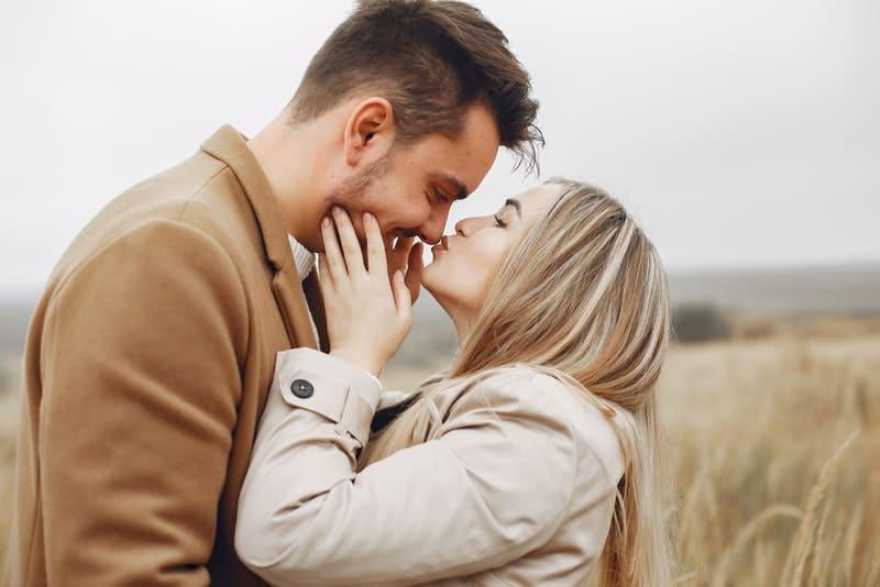 en flicka i en grå kappa i ett gräsfält kysser sin man på näsan