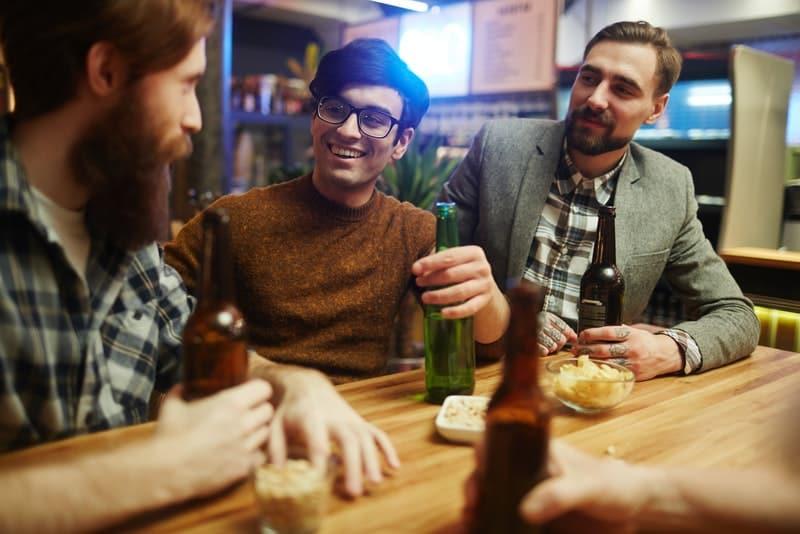 en grupp vänner i en bar som pratar och dricker öl
