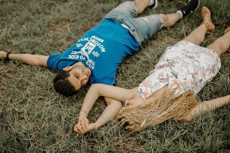 en man i en blå T-shirt som törstade på gräset med en kvinna i en vit klänning