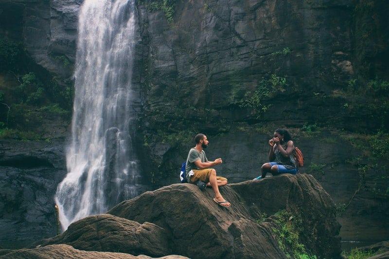 en man och en kvinna sitter på en klippa nära ett vattenfall