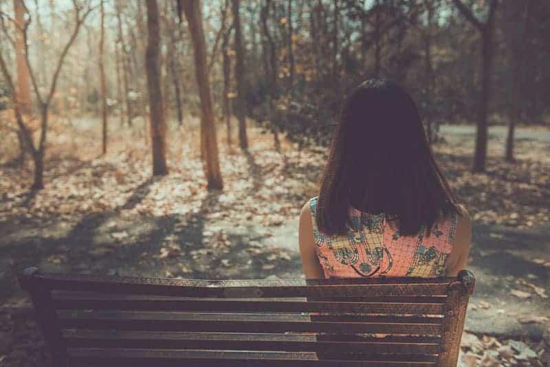 ensam kvinnasammanträde på bänken i parken