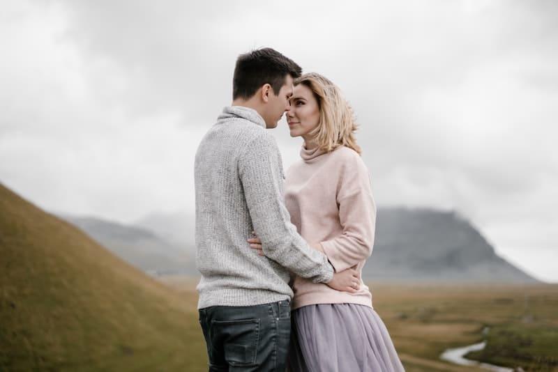 ett kärleksfullt par som står i en omfamning på en äng och tittar in i varandras ögon