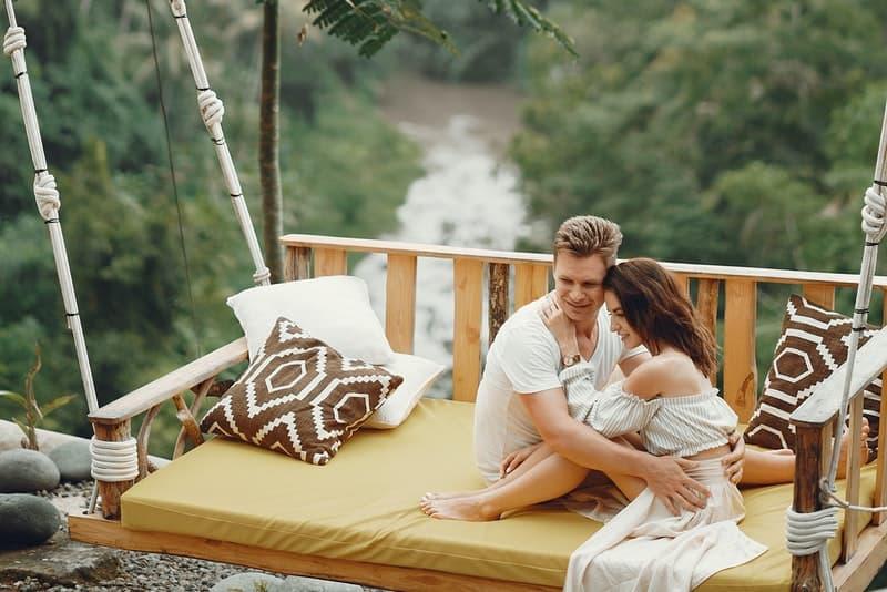 ett leende älskande par som sitter i en omfamning på en gunga