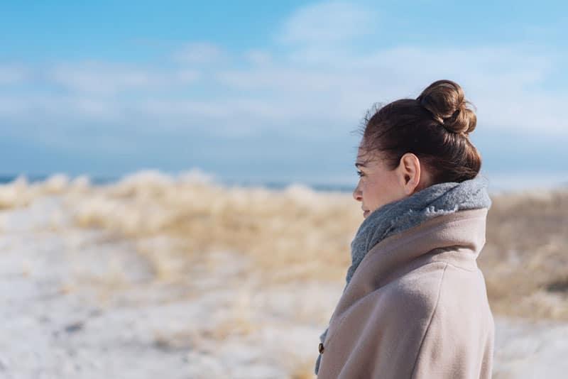 kvinna i kappa som står utomhus