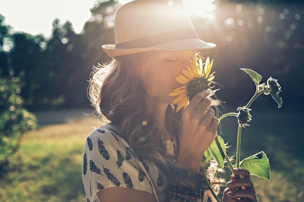 kvinna i stråhatt som luktar blomman