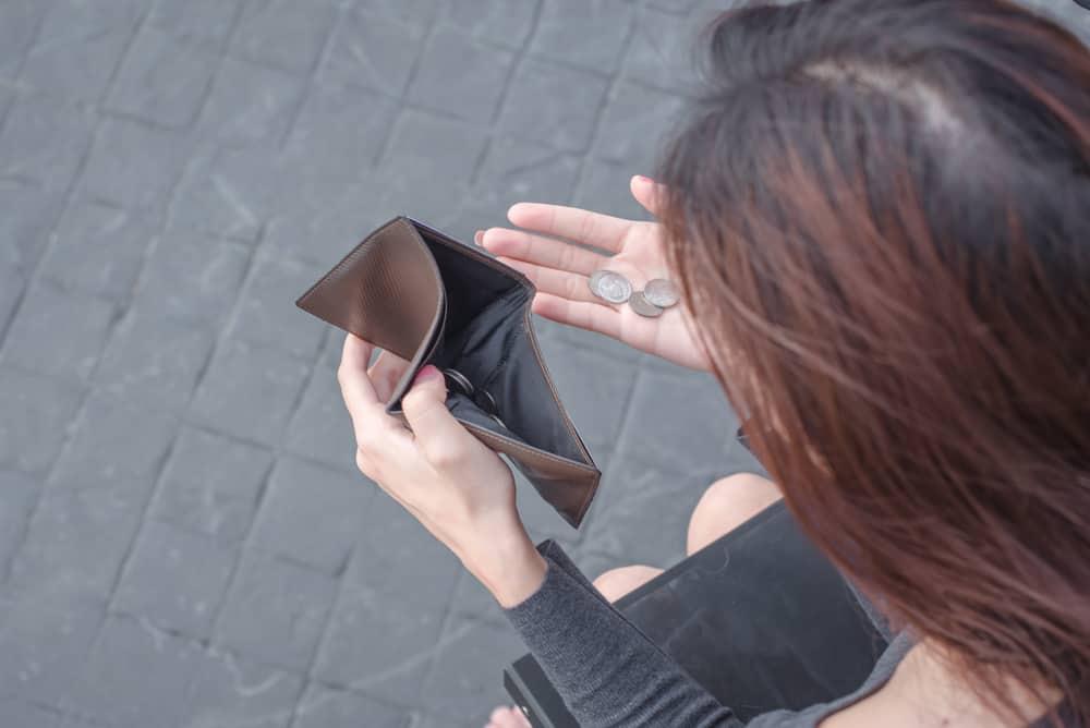 kvinna med tom plånbok