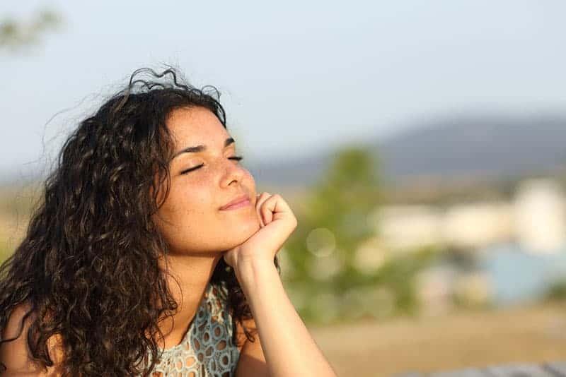 le kvinna stående utomhus med slutna ögon