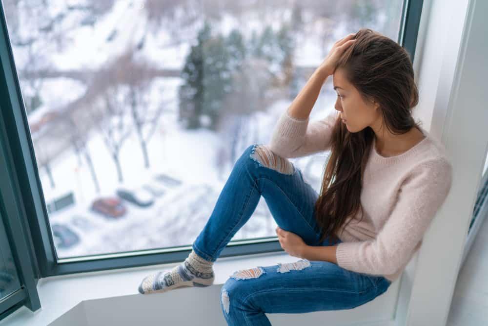 ledsen kvinna tittar på snö