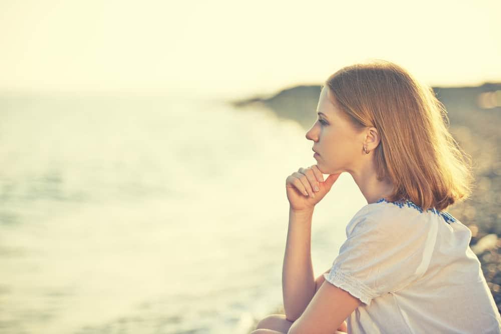 ledsen tjej som sitter vid kusten på stranden och tittar på avståndet till havs