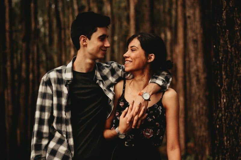 man kramar kvinnan och ler