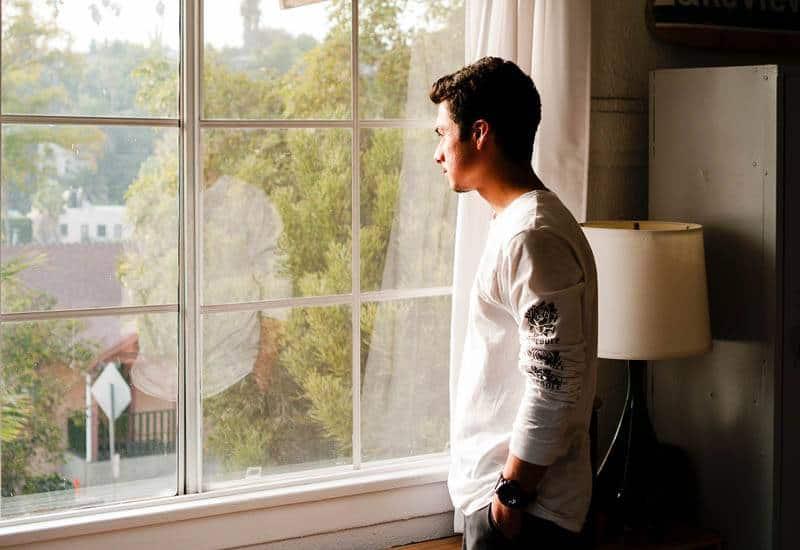mannen i vit t-shirt står bredvid fönstret och tittar ut