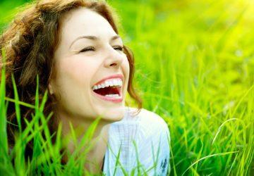 vacker lycklig kvinna som ligger i gräset