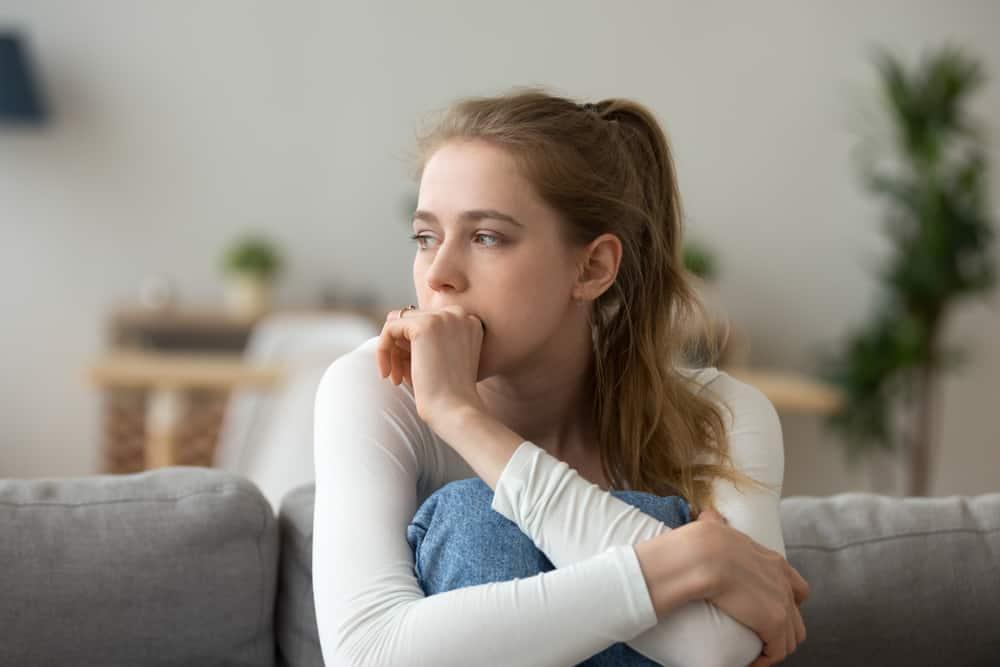 orolig kvinna som sitter på soffan