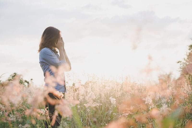 sorglig kvinna som står i fältet