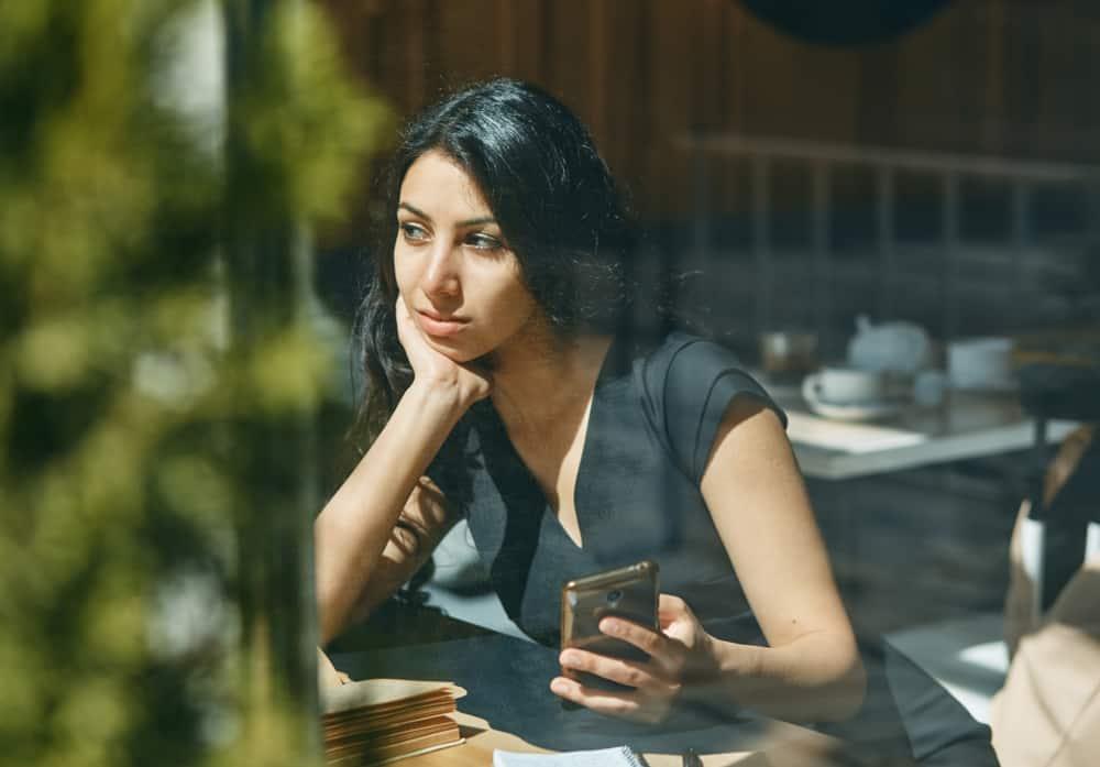 ung kvinna i café som håller telefonen och tittar på avstånd