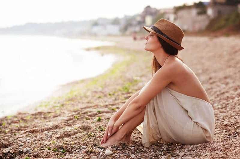 ung kvinna med hatt sitter på stranden