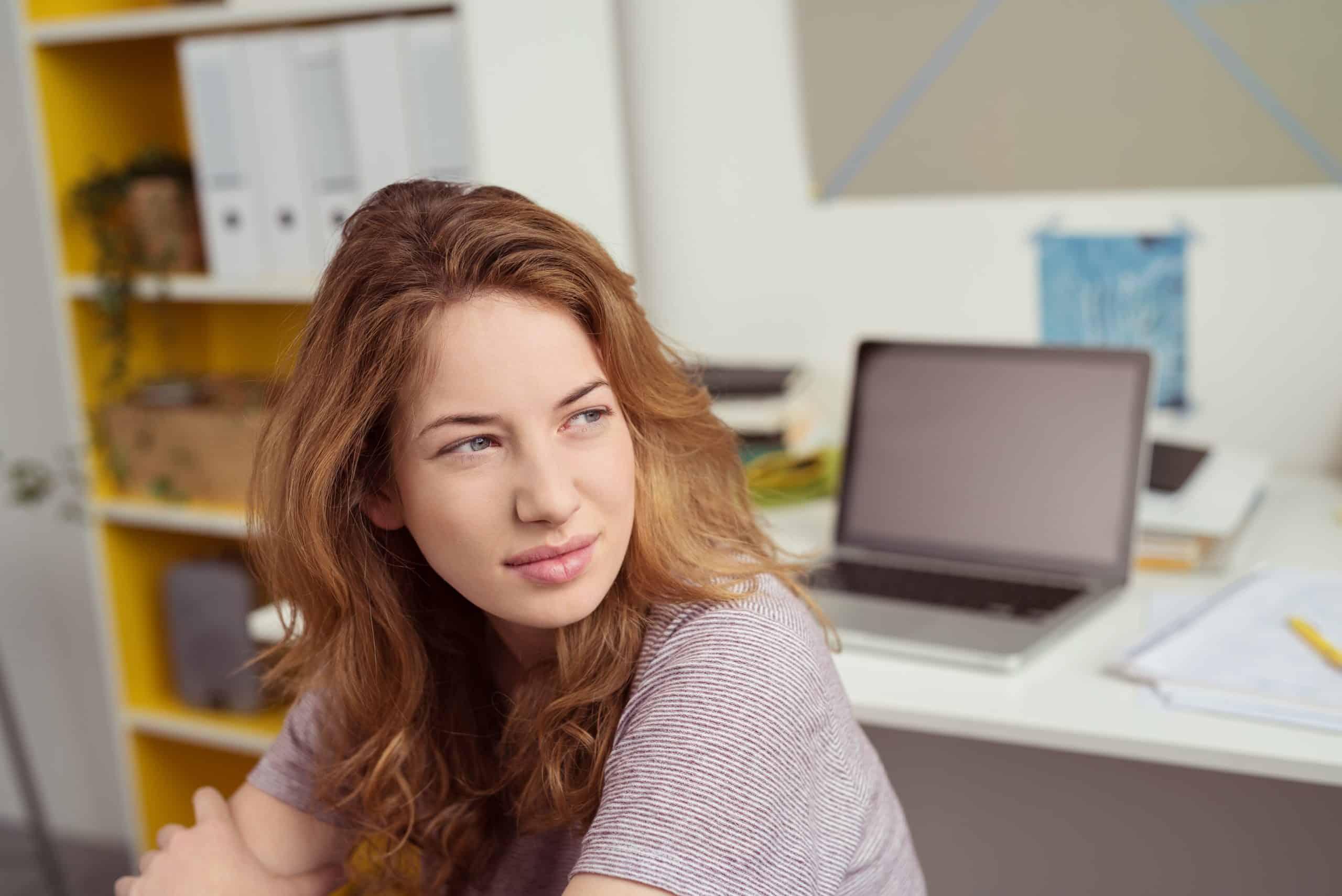 ung kvinna på jobbet tittar på avstånd