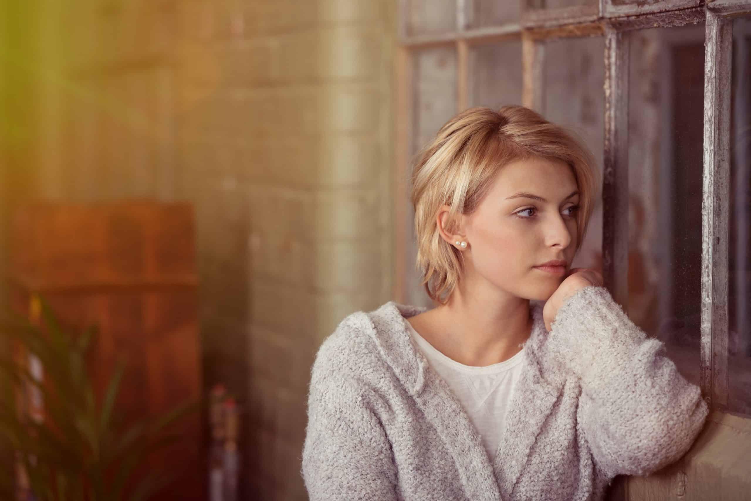 ung kvinna stirrar ut genom ett fönster i vardagsrummet med ett allvarligt uttryck