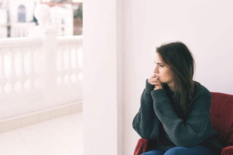 ung kvinna tittar genom balkongfönstret