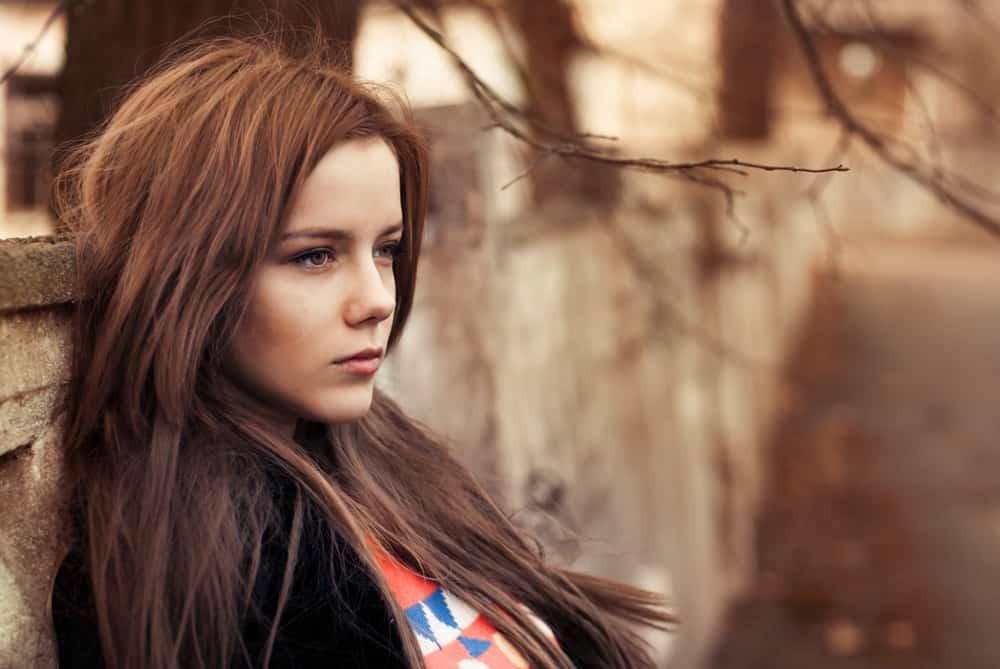 vacker flicka sitter utanför och tittar på avstånd