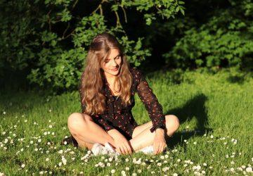 en glad kvinna i en svart sommarklänning sitter på gräset