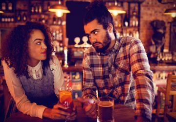 en man och en kvinna står vid ett hängande bord på ett kafé och tittar på varandra