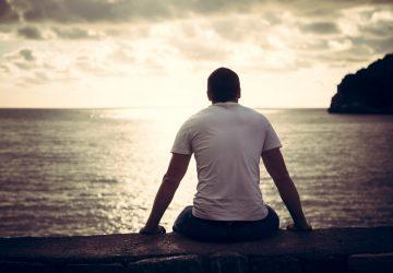 man sitter ensam och tittar på stranden