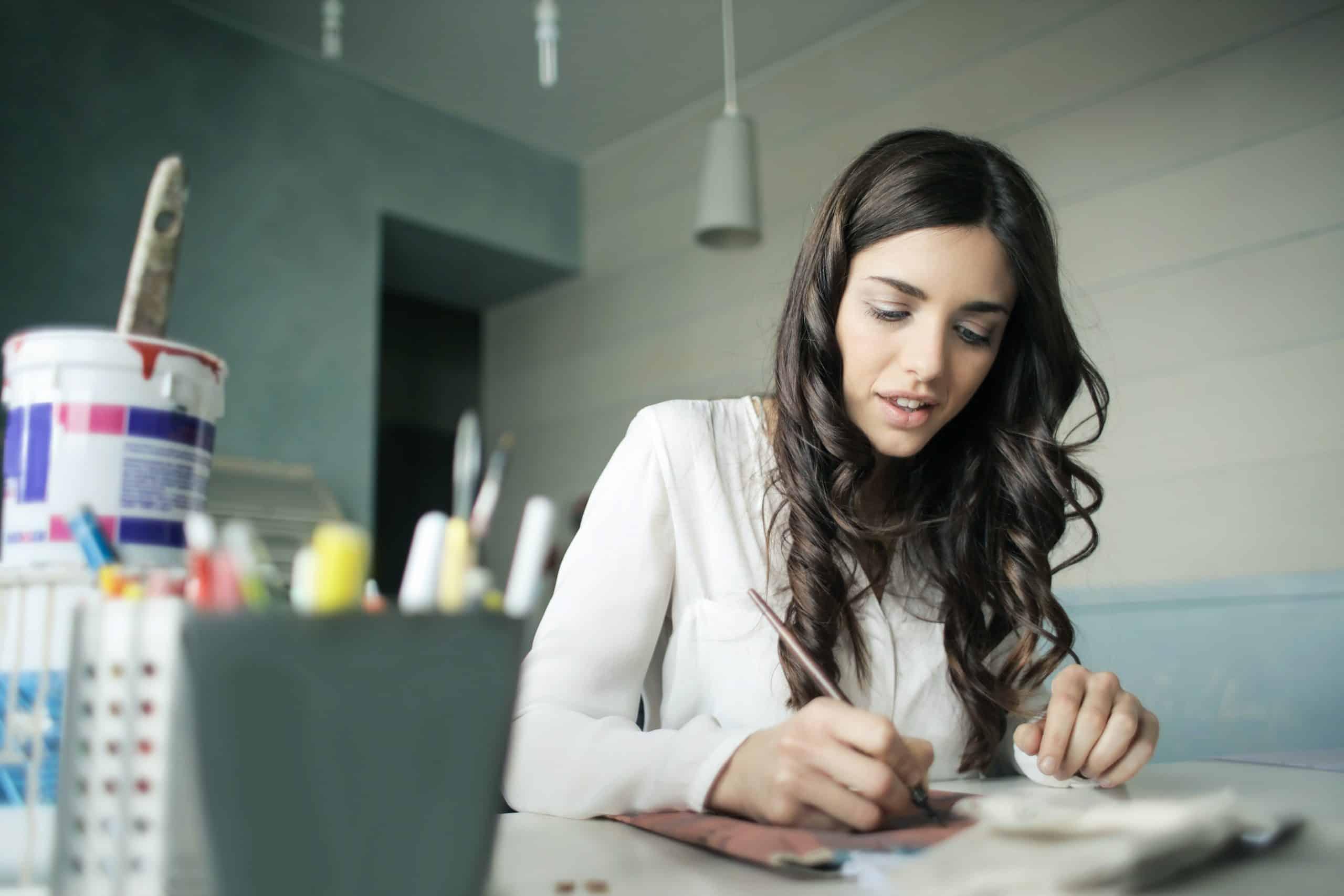 kvinna i vit skjorta skriver