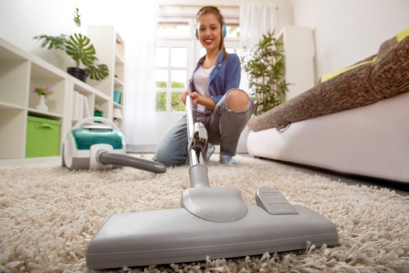 Kvinna med dammsugare som gör ren mattan hemma