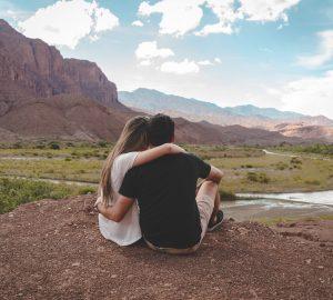 man och kvinna som kramar i naturen