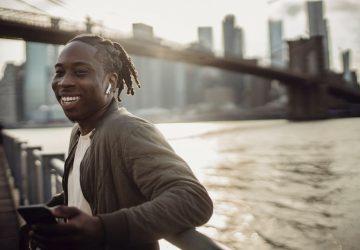 en humör leende svart man står på bron med en telefon i handen