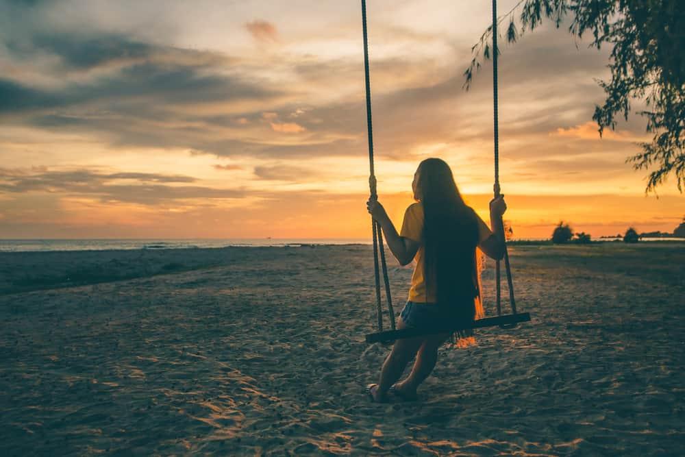 Silhuetten av en ensam ung kvinna som svänger på stranden vid solnedgången