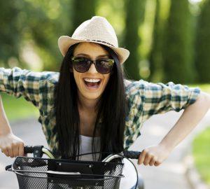 Lycklig ung kvinna med cykel