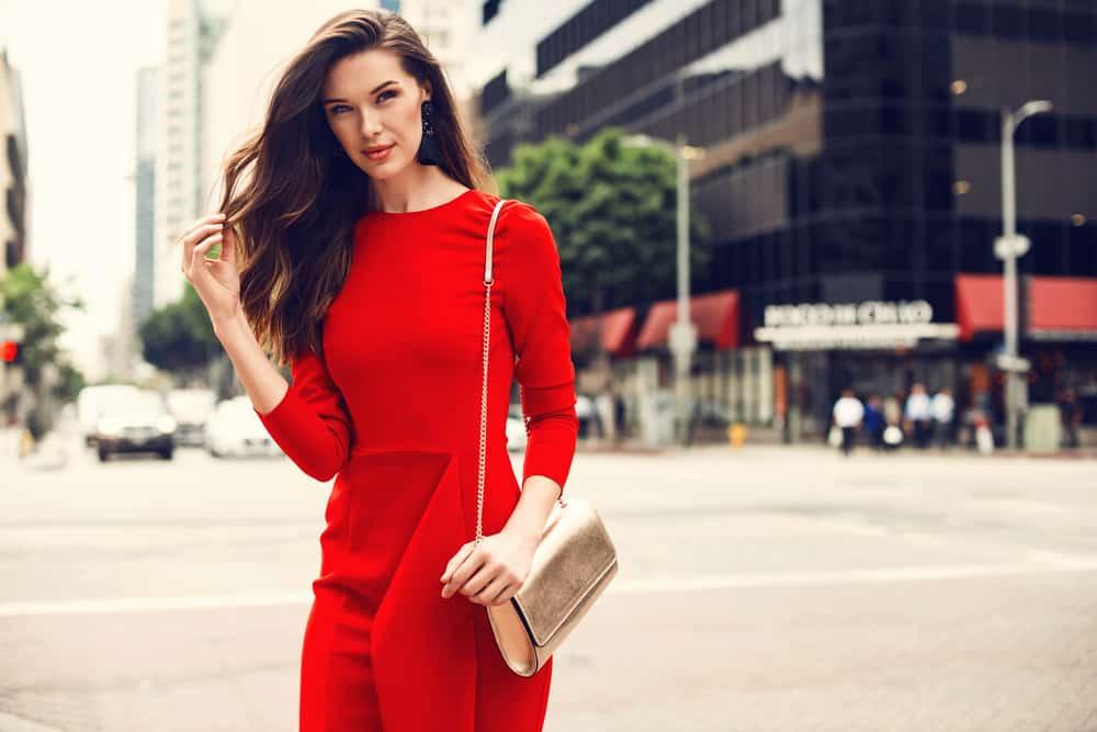 Ung kvinna för härlig brunett som bär röd klänning