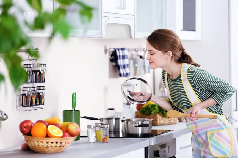 Ung kvinna som lagar mat i köket