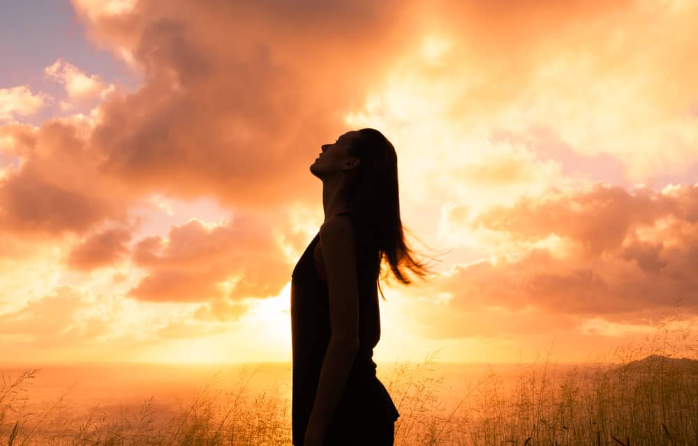 Ung kvinna som ser upp i himlen