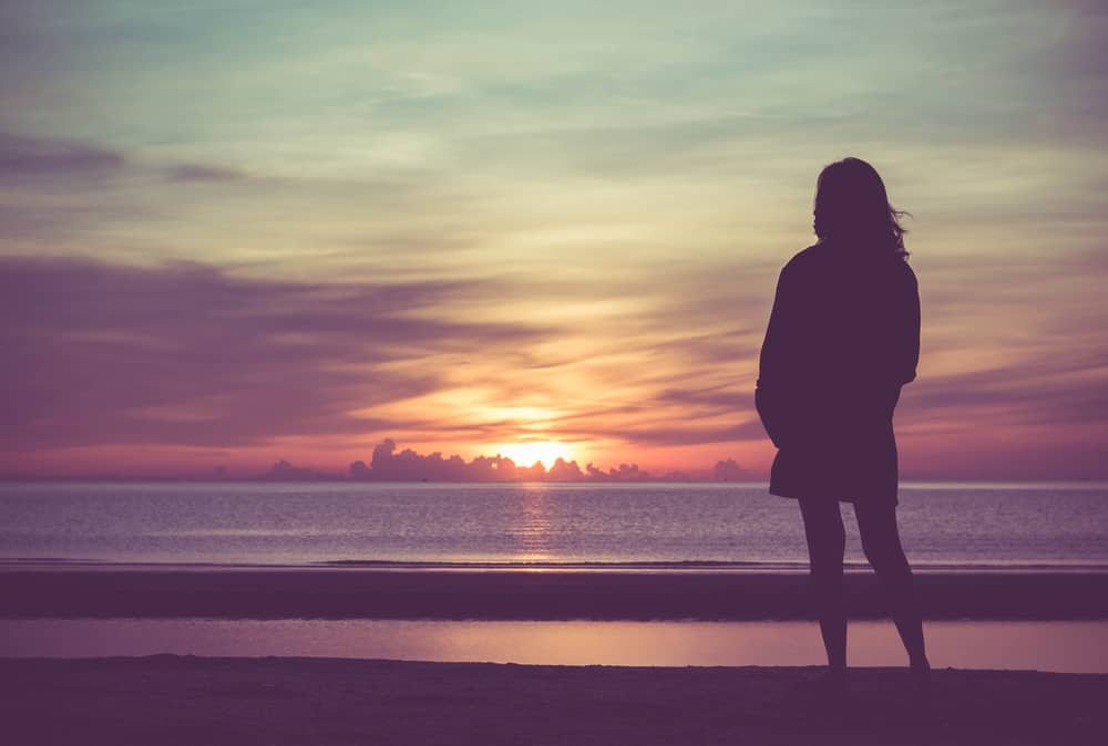 Ung kvinna som står på stranden i havet och ser till soluppgång