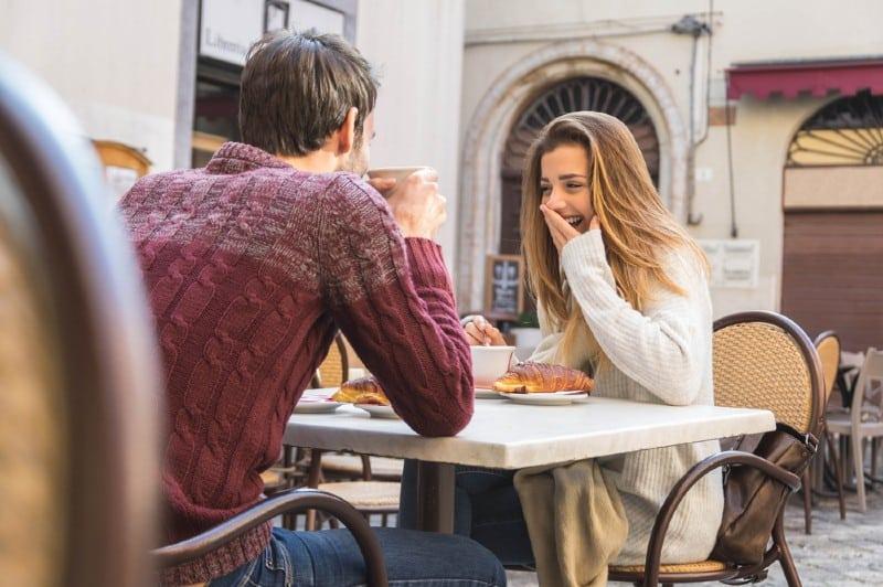 Ungt par som talar på kaféen på ett datum.