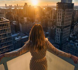 kvinna njuter av solnedgången som står på balkongen